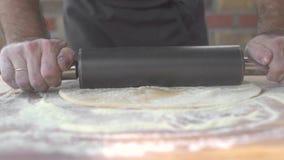 Μάγειρας που ψεκάζει το αλεύρι και που κυλά λεπτή τη ζύμη με την καρφίτσα κυλίνδρων στον πίνακα κουζινών Μαγειρεύοντας ζύμη πιτών απόθεμα βίντεο