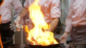 Μάγειρες αρχιμαγείρων και να κάνει flambe στην μπριζόλα βόειου κρέατος στο τηγάνι σχαρών στην κουζίνα εστιατορίων φιλμ μικρού μήκους