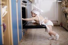 Μάγειρες αρχιμαγείρων μωρών στα τρόφιμα φούρνων Στοκ Φωτογραφία