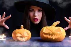 Μάγισσα αποκριών με μια μαγική κολοκύθα Όμορφη νέα γυναίκα στο καπέλο μαγισσών και τη χαρασμένη εκμετάλλευση κολοκύθα κοστουμιών  Στοκ Φωτογραφίες