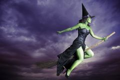 Μάγισσα αποκριών που πετά στο σκουπόξυλο Στοκ Φωτογραφίες