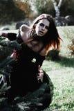 Μάγισσα αποκριών σε μια μελαχροινή δασική όμορφη νέα γυναίκα στο κοστούμι μαγισσών Σχέδιο τέχνης αποκριών Υπόβαθρο φρίκης για απο Στοκ Εικόνες