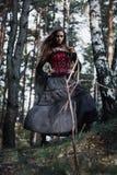Μάγισσα αποκριών σε μια μελαχροινή δασική όμορφη νέα γυναίκα στο κοστούμι μαγισσών Σχέδιο τέχνης αποκριών Υπόβαθρο φρίκης για απο Στοκ Φωτογραφία