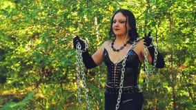 Μάγισσα γυναικών στα μαύρα ενδύματα με μια αλυσίδα διαθέσιμη στο δάσος απόθεμα βίντεο