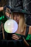 μάγισσα σε ένα μαύρο υπόβαθρο με μια μαγική σφαίρα Στοκ Φωτογραφίες