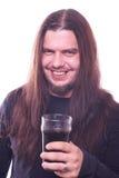 Μάγκα με τη ρέοντας τρίχα που χαμογελά και που κρατά το γυαλί μπύρας στοκ φωτογραφία με δικαίωμα ελεύθερης χρήσης