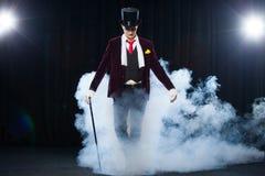 Μάγος, άτομο ζογκλέρ, αστείο πρόσωπο, μαύρος μαγικός, παραίσθηση που στέκεται στο στάδιο με έναν κάλαμο του όμορφου φωτός Στοκ Εικόνες
