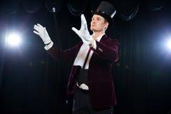 Μάγος με τη σφαίρα μυγών, άτομο ζογκλέρ, αστείο πρόσωπο, μαύρος μαγικός, εστίαση παραίσθησης Α με έναν levitating κάλαμο με έναν  Στοκ Φωτογραφία