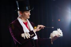 Μάγος με το κουνέλι, άτομο ζογκλέρ, αστείο πρόσωπο, μαύρος μαγικός, παραίσθηση σε ένα μαύρο υπόβαθρο Στοκ φωτογραφία με δικαίωμα ελεύθερης χρήσης