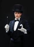 Μάγος στο τοπ καπέλο με τη μαγική ράβδο που παρουσιάζει τέχνασμα Στοκ Φωτογραφίες