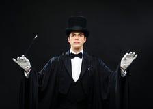 Μάγος στο τοπ καπέλο με τη μαγική ράβδο που παρουσιάζει τέχνασμα Στοκ εικόνα με δικαίωμα ελεύθερης χρήσης