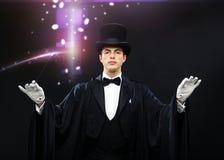 Μάγος στο τοπ καπέλο με τη μαγική ράβδο που παρουσιάζει τέχνασμα Στοκ Εικόνα