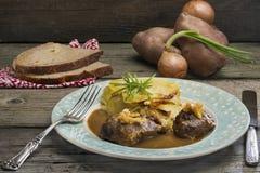 Μάγουλα χοιρινού κρέατος στο ζωμό με τα καραμελοποιημένα πράσα και το κέικ ουαλλέζικων κρεμμυδιών Στοκ Εικόνες