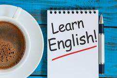 Μάθετε τα αγγλικά - σημειώστε στο μπλε υπόβαθρο με την κούπα καφέ πρωινού στοκ εικόνες