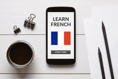 Μάθετε τη γαλλική έννοια στην έξυπνη τηλεφωνική οθόνη με τα αντικείμενα γραφείων Στοκ Φωτογραφία