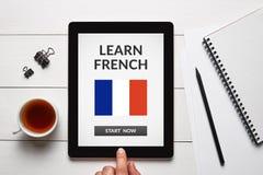 Μάθετε τη γαλλική έννοια στην οθόνη ταμπλετών με τα αντικείμενα γραφείων Στοκ εικόνα με δικαίωμα ελεύθερης χρήσης