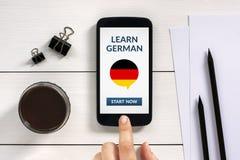 Μάθετε τη γερμανική έννοια στην έξυπνη τηλεφωνική οθόνη με τα αντικείμενα γραφείων Στοκ φωτογραφία με δικαίωμα ελεύθερης χρήσης