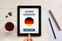 Μάθετε τη γερμανική έννοια στην οθόνη ταμπλετών με τα αντικείμενα γραφείων Στοκ Εικόνες