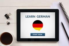 Μάθετε τη γερμανική έννοια στην οθόνη ταμπλετών με τα αντικείμενα γραφείων Στοκ εικόνα με δικαίωμα ελεύθερης χρήσης