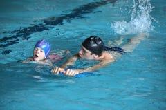 Μάθημα κολύμβησης - λάκτισμα κυματισμού άσκησης παιδιών με την επιτροπή λακτίσματος με τον εκπαιδευτικό Στοκ εικόνα με δικαίωμα ελεύθερης χρήσης