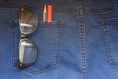 Μάνδρα γυαλιών στο πίσω τζιν παντελόνι στοκ εικόνα