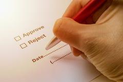 Μάνδρα εκμετάλλευσης χεριών που υπογράφει Approve ή το απόρριμα στο έγγραφο Στοκ εικόνες με δικαίωμα ελεύθερης χρήσης