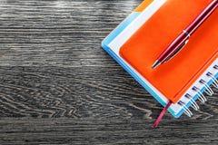 Μάνδρα σημειωματάριων ballpoint στην ξύλινη τοπ άποψη πινάκων Στοκ Εικόνες