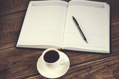 Μάνδρα στο σημειωματάριο και τον καφέ στοκ φωτογραφία