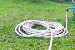Μάνικα κήπων ή άσπρος λαστιχένιος σωλήνας με τη στρόφιγγα στον τομέα χλόης Στοκ φωτογραφία με δικαίωμα ελεύθερης χρήσης