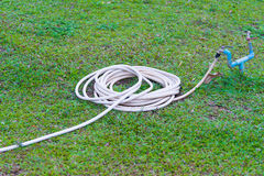 Μάνικα κήπων ή άσπρος λαστιχένιος σωλήνας με τη στρόφιγγα στον τομέα χλόης Στοκ εικόνες με δικαίωμα ελεύθερης χρήσης
