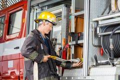 Μάνικα νερού καθορισμού πυροσβεστών στο φορτηγό στην πυρκαγιά Στοκ Φωτογραφίες