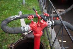 Μάνικα πυρκαγιάς που γαντζώνεται μέχρι ένα σκουριασμένο κόκκινο στόμιο υδροληψίας πυρκαγιάς Στοκ φωτογραφία με δικαίωμα ελεύθερης χρήσης