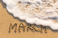 Μάρτιος - λέξη που επισύρεται την προσοχή στην παραλία άμμου με το μαλακό κύμα στοκ εικόνες με δικαίωμα ελεύθερης χρήσης