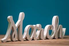 Μάρτιος - λέξη που χαράζεται του ξύλου μήνας άνοιξη Μαρτίου πρώτος, ημερολόγιο στο μπλε υπόβαθρο στοκ φωτογραφία