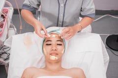 Μάσκα κολλαγόνων επεξεργασία δερμάτων πυράκτωσης που χρησιμοποιεί τη χρυσή μάσκα Στοκ Εικόνες