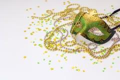 Μάσκες και χάντρες καρναβαλιού πράσινες και χρυσές σε ένα άσπρο υπόβαθρο Στοκ Εικόνες
