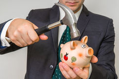 Μάταιος επιχειρηματίας που σπάζει τη piggy τράπεζα με το σφυρί στοκ εικόνες