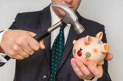 Μάταιος επιχειρηματίας που σπάζει τη piggy τράπεζα με το σφυρί στοκ φωτογραφία