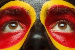 Μάτια του γερμανικού ή βελγικού πατριώτη αθλητικών ανεμιστήρων Χρωματισμένη σημαία χωρών στο πρόσωπο ατόμων Στοκ Εικόνες