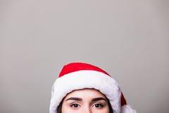 Μάτια του κοριτσιού στο καπέλο santa στο γκρίζο υπόβαθρο στοκ φωτογραφία