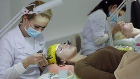 Μάτι γυναικών με τα μακροχρόνια eyelashes Επέκταση Beautician eyelash για τη νέα γυναίκα σε ένα σαλόνι ομορφιάς φιλμ μικρού μήκους
