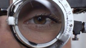 Μάτι γυναικών με τον αλλαγμένο φακό στο phoropter, δοκιμή οπτικής οξύτητας, διαγνωστικά κερατοειδών χιτώνων φιλμ μικρού μήκους