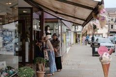 Μέλη των δημόσιων βλέπων παγωτών αγοράς σε έναν μετρητή σε μια αγγλική κεντρική οδό στοκ φωτογραφία