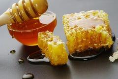 Μέλι και κηρήθρα σε ένα μαύρο υπόβαθρο Στοκ Φωτογραφία