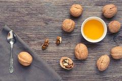 Μέλι με τα καρύδια σε μια ξύλινη επιφάνεια με μια πετσέτα και ένα κουτάλι επάνω από την όψη Στοκ Φωτογραφίες