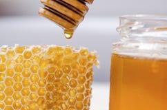 Μέλι που στάζει από ένα ξύλινο κουτάλι επάνω στη χτένα μελιού στοκ φωτογραφία με δικαίωμα ελεύθερης χρήσης