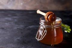 Μέλι που στάζει από dipper στο σύνολο βάζων του φρέσκου μελιού στο σκοτεινό υπόβαθρο πετρών στοκ φωτογραφία