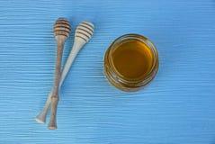Μέλι σε ένα βάζο γυαλιού και δύο κουτάλια σούπας για το μέλι σε έναν πίνακα Στοκ Εικόνα