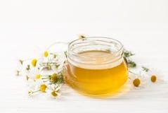 Μέλι σε ένα βάζο με τα chamomile λουλούδια σε έναν άσπρο πίνακα Στοκ φωτογραφία με δικαίωμα ελεύθερης χρήσης