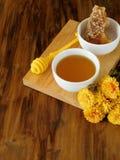 Μέλι σε ένα λευκό λίγο κύπελλο σε έναν ξύλινο πίνακα Στοκ φωτογραφίες με δικαίωμα ελεύθερης χρήσης